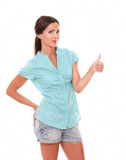 Friendly latin female with thumb up. Gesturing ok sign while looking at you standing in white background Stock Photos