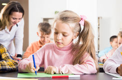 Friendly little kids with teacher drawing in classroom. On the lesson Stock Photos