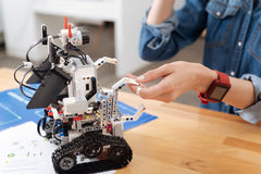 Friendly little robot making friends with human indoors Royalty Free Stock Photography