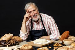 Elderly smiling professional chef man. Isolated over black background royalty free stock image