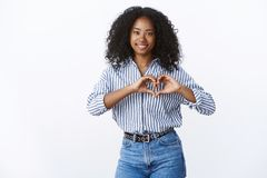 Friendly-looking charming happy young dark-skinned female showing heart gesture romantic love sign smiling broadly. Feeling sympathy confessing boyfriend royalty free stock images