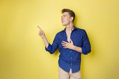 Friendly looking cheerful european guy with dark hair wearing blue shirt, smiling widely, pointing left while standing royalty free stock images