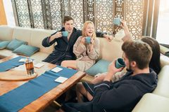 Relaxed diverse friends in bathrobes sitting at lounge zone of bathhouse. Friendly looking group of young men and women visit spa centre to celebrate b-day royalty free stock photos