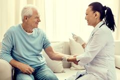 Friendly looking nurse vaccinating cheerful retired man. Supporting immune system. Positive minded medical worker beaming while looking at an elderly gentleman Royalty Free Stock Photos