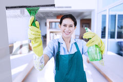 Friendly maid cleaning a mirror Stock Image