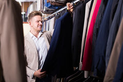 Friendly male customer examining men's suits. Friendly male customer examining suits in men's cloths store Stock Photo
