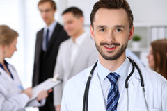 Friendly male doctor on the background doctor and many patients.  stock photo