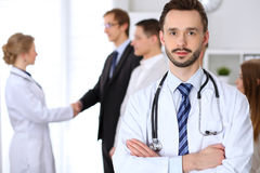 Friendly male doctor on the background doctor and patient shaking hands. Medical trust and ethics concept Stock Photos