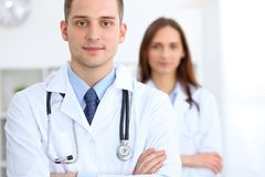 Friendly male doctor on the background of female physician in hospital office. Ready to examine and help patients. High level and quality medical service Stock Photo