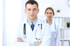 Friendly male doctor on the background of female physician in hospital office. Ready to examine and help patients. High level and quality medical service Stock Image