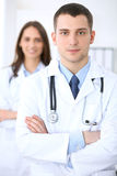 Friendly male doctor on the background of female physician in hospital office. Ready to examine and help patients. High level and quality medical service Royalty Free Stock Image