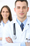 Friendly male doctor on the background of female physician in hospital office. Ready to examine and help patients. High level and quality medical service Royalty Free Stock Photo