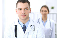 Friendly male doctor on the background of female physician in hospital office. Ready to examine and help patients. High level and quality medical service Stock Photography