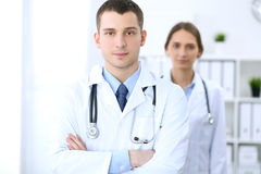 Friendly male doctor on the background of female physician in hospital office. Ready to examine and help patients. High level and quality medical service Royalty Free Stock Images