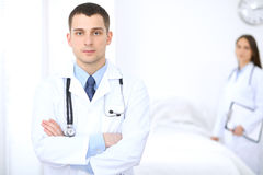 Friendly male doctor on the background of female physician in hospital. Ready to examine and help patients. High level and quality medical service concept Stock Photo