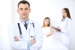 Friendly male doctor on the background with patient in the bed and his physician.  Royalty Free Stock Image