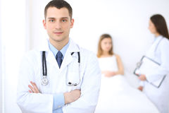 Friendly male doctor on the background with patient in the bed and his physician.  Stock Photos