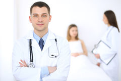 Friendly male doctor on the background with patient in the bed and his physician.  Royalty Free Stock Images