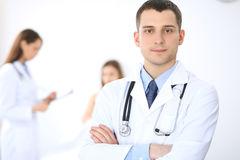 Friendly male doctor on the background with patient in the bed and his physician.  Stock Images