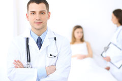Friendly male doctor on the background with patient in the bed and his physician.  Stock Photography