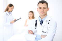 Friendly male doctor on the background with patient in the bed and his physician.  Stock Image