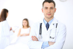 Friendly male doctor on the background with patient in the bed and his physician.  Royalty Free Stock Photo