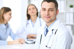 Friendly male doctor  on the background with patient and her physician in hospital office. High level and quality medical service concept Stock Photos
