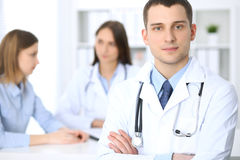 Friendly male doctor  on the background with patient and her physician in hospital office. High level and quality medical service concept Royalty Free Stock Image