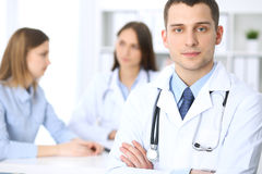 Friendly male doctor  on the background with patient and her physician in hospital office. High level and quality medical service concept Royalty Free Stock Photos