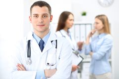 Friendly male doctor on the background with patient and physician royalty free stock photo