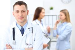 Friendly male doctor  on the background with patient  and physician Royalty Free Stock Images