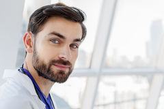 Friendly male doctor expressing positive emotions. You can trust me. Kind young general practitioner is looking at camera with confidence Royalty Free Stock Photo