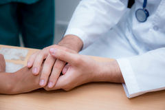 Friendly male doctor hand holding patient hand sitting at the de royalty free stock photos