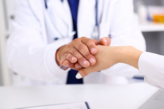 Friendly male doctor hold female arm in office Stock Photos