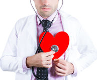 Friendly male doctor holding and listening to a heart with a stethoscope Stock Images