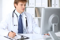 Friendly male doctor is sitting at the table and working in the hospital office. Ready to examine and help patients Stock Photos