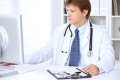 Friendly male doctor is sitting at the table and working in the hospital office. Ready to examine and help patients Stock Image