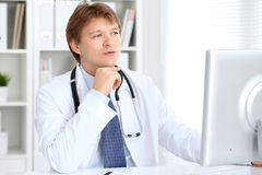 Friendly male doctor is sitting at the table and working in the hospital office. Ready to examine and help patients Stock Photography