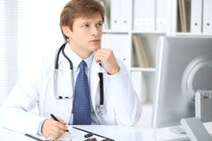 Friendly male doctor is sitting at the table and working in the hospital office. Ready to examine and help patients Stock Images