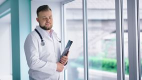 Friendly male doctor standing next large window at hospital corridor holding folder in his hands stock footage