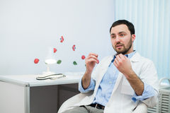 Friendly male medicine therapeutist doctor sitting in office, talking patient and looking to camera. Medical help Stock Photo