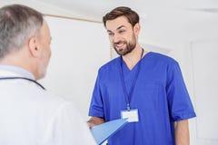 Friendly male nurse handing folder to doctor stock photography