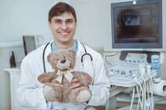 Friendly male pediatrician working at the clinic stock image