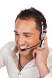 Friendly male receptionist or call centre operator. Listening carefully to a call on his headset as he deals with support and public relations for the company Royalty Free Stock Image