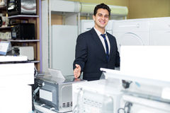Friendly male seller at household appliances section Stock Images