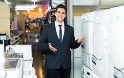 Friendly male seller at household appliances section Royalty Free Stock Photos