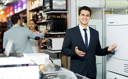Friendly male seller at household appliances section Stock Image