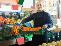 Friendly male seller offers mandarins Royalty Free Stock Images