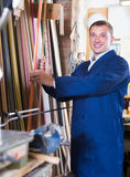 Friendly male seller in picture framing studio with wooden detai. Friendly male seller standing in picture framing studio with wooden details Royalty Free Stock Image