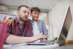 Friendly male teacher helping his little student stock image